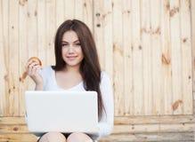 Muchacha sonriente con la computadora portátil y la manzana Fotos de archivo libres de regalías