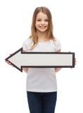 Muchacha sonriente con la flecha en blanco que señala a la izquierda Fotografía de archivo