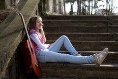 Muchacha sonriente con la guitarra que se sienta en las escaleras en parque y que descansa sobre Sunny Spring Day Fotografía de archivo