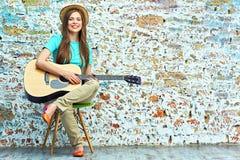 Muchacha sonriente con la guitarra que se sienta en silla Imágenes de archivo libres de regalías
