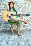 Muchacha sonriente con la guitarra que se sienta en silla Fotos de archivo libres de regalías