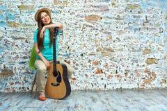 Muchacha sonriente con la guitarra que se sienta en silla Foto de archivo