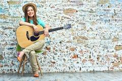 Muchacha sonriente con la guitarra que se sienta en silla Fotografía de archivo