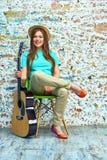 Muchacha sonriente con la guitarra que se sienta en silla Imagen de archivo libre de regalías