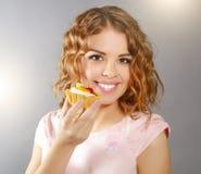Muchacha sonriente con la magdalena Imagenes de archivo