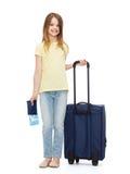 Muchacha sonriente con la maleta, el boleto y el pasaporte Fotos de archivo libres de regalías