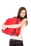Muchacha sonriente con la maleta en un fondo blanco Fotografía de archivo
