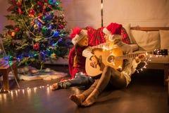 Muchacha sonriente con la mamá cerca del árbol de navidad en casa Imagen de archivo libre de regalías