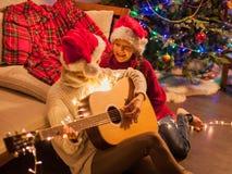 Muchacha sonriente con la mamá cerca del árbol de navidad en casa Imagen de archivo