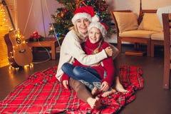 Muchacha sonriente con la mamá cerca del árbol de navidad en casa Foto de archivo