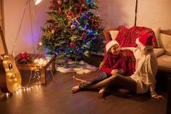Muchacha sonriente con la mamá cerca del árbol de navidad en casa Imágenes de archivo libres de regalías