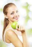 Muchacha sonriente con la manzana verde Fotografía de archivo