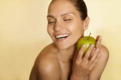 Muchacha sonriente con la manzana verde Foto de archivo