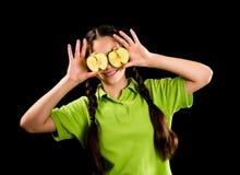 Muchacha sonriente con la manzana verde en ojos Imagenes de archivo