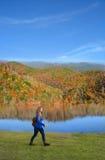 Muchacha sonriente con la mochila que camina en las montañas del otoño Foto de archivo