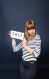 Muchacha sonriente con la muestra de la venta Imagenes de archivo
