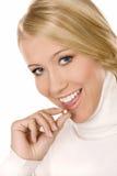 Muchacha sonriente con la píldora aislada en blanco Imagenes de archivo