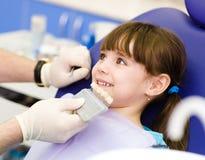 Muchacha sonriente con la paleta para el color del diente Imágenes de archivo libres de regalías