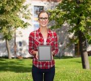 Muchacha sonriente con la pantalla en blanco de la PC de la tableta Foto de archivo