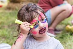 Muchacha sonriente con la pintura del arte de la cara como tigre, niño pequeño que hace la pintura de la cara, partido de Hallowe fotografía de archivo