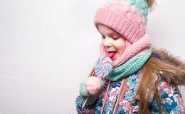Muchacha sonriente con la piruleta en ropa del invierno Fotos de archivo