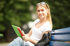 Muchacha sonriente con la sentada de la tableta y de la mochila Foto de archivo libre de regalías