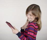 Muchacha sonriente con la tableta digital Foto de archivo libre de regalías