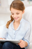 Muchacha sonriente con la tableta en casa Foto de archivo libre de regalías