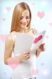 Muchacha sonriente con la tarjeta de la tarjeta del día de San Valentín Foto de archivo