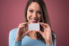 Muchacha sonriente con la tarjeta de visita Fotografía de archivo