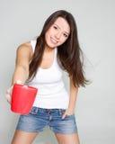 Muchacha sonriente con la taza de té roja Fotografía de archivo libre de regalías