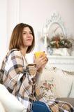 Muchacha sonriente con la taza en el sofá Fotografía de archivo libre de regalías
