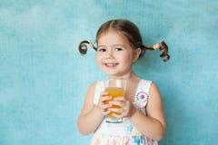 Muchacha sonriente con las coletas divertidas con el vidrio de jugo Imagen de archivo libre de regalías