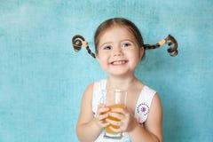 Muchacha sonriente con las coletas divertidas con el vidrio de jugo Fotografía de archivo libre de regalías