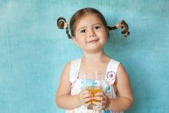 Muchacha sonriente con las coletas divertidas con el vidrio de jugo Foto de archivo libre de regalías