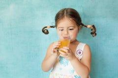 Muchacha sonriente con las coletas divertidas con el vidrio de jugo Fotos de archivo libres de regalías