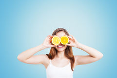 Muchacha sonriente con las naranjas en fondo azul Imagenes de archivo