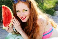 Muchacha sonriente con las pecas que sostienen la sandía Imagen de archivo