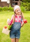 Muchacha sonriente con las verduras frescas en cesta Foto de archivo