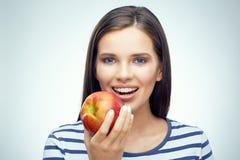 Muchacha sonriente con los apoyos dentales que sostienen la manzana roja Imágenes de archivo libres de regalías