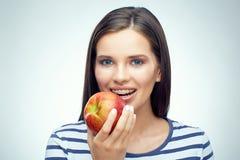 Muchacha sonriente con los apoyos dentales que sostienen la manzana roja Foto de archivo libre de regalías