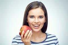Muchacha sonriente con los apoyos dentales que sostienen la manzana roja Fotografía de archivo