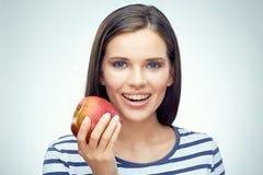 Muchacha sonriente con los apoyos dentales que sostienen la manzana roja Imagenes de archivo