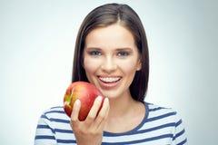 Muchacha sonriente con los apoyos dentales que sostienen la manzana roja Foto de archivo