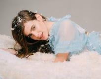 Muchacha sonriente con los apoyos en el camisón azul del cordón que miente en cama suave Muchacha alegre con el pelo moreno largo Foto de archivo libre de regalías