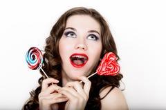 Muchacha sonriente con los apoyos que sostienen el caramelo del corazón que presenta en un fondo blanco Fotografía de archivo