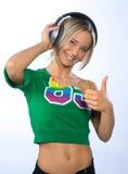 Muchacha sonriente con los auriculares Foto de archivo libre de regalías