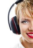 Muchacha sonriente con los auriculares aislados en blanco Foto de archivo