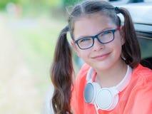 Muchacha sonriente con los auriculares al aire libre Foto de archivo