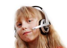 Muchacha sonriente con los auriculares en el fondo blanco. Fotografía de archivo